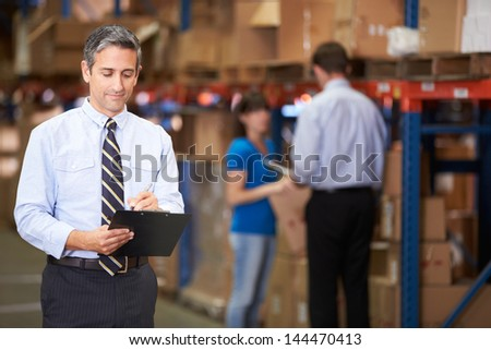 Manager In Warehouse Writing On Clipboard - stock photo