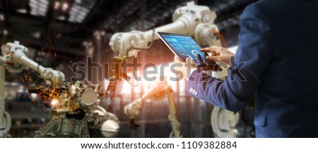 Manager industrial engineer using tablet check and control automation robot arms machine in intelligent factory. Welding robotics and digital manufacturing operation. Industry 4.0 concept