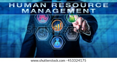 Manager is pushing HUMAN RESOURCE MANAGEMENT on an interactive touch screen. Business metaphor and management concept for workforce planning, recruitment, career development and compensation.