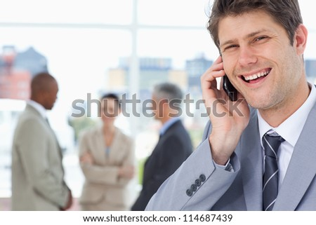 Manager laughing while using his mobile phone