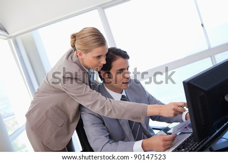 Manager pointing at something to her secretary on a computer in his office