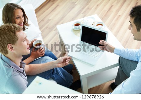 Manager presenting insurance program terms to young couple
