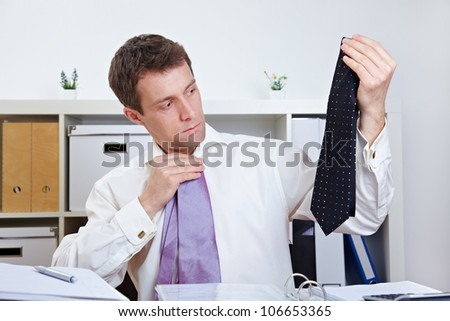 Manager selecting a tie at his desk in the office