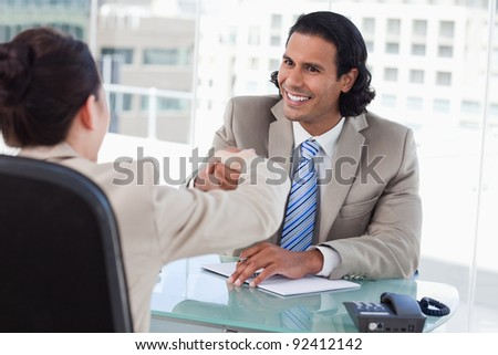 Manager shaking the hand of a female applicant in his office