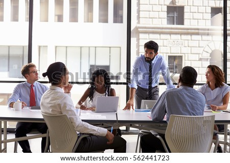 Manager standing to address colleagues at a business meeting - Shutterstock ID 562441723