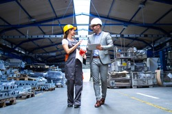 Manager supervisor and industrial worker in uniform walking in large metal factory hall and talking about increasing production.