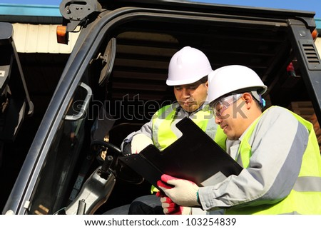manager talking with forklift operator on warehouse