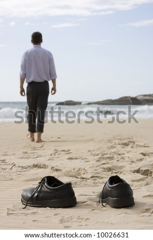 Manager walking barefoot on the beach. Focus on the shoes in the foreground