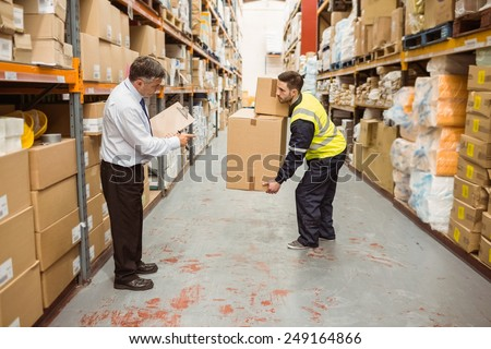Manager watching worker carrying boxes in a large warehouse #249164866