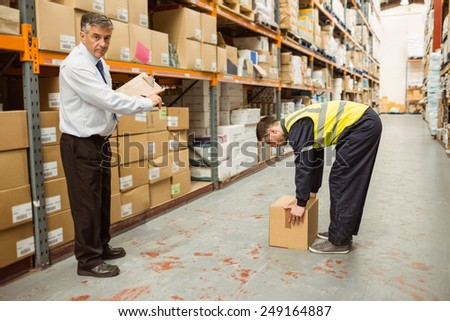Manager watching worker carrying boxes in a large warehouse #249164887