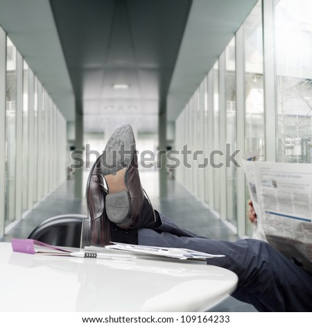 manager with feet on desk reading newspaper
