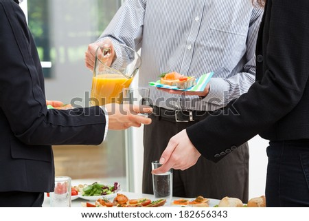 Manager with jug of orange juice and sandwiches
