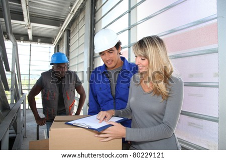 Manager with store-men controlling goods delivery