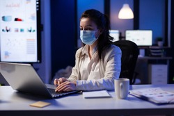 Manager woman with face mask working overtime in new normal business office looking at team project on professional laptop. Analysing financial documents sitting at desk during global pandemic