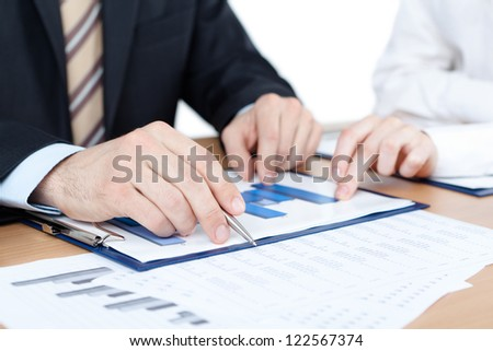Manager working with diagrams. Close up of hands and documents