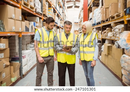 Manager writing on clipboard talking to colleague in a large warehouse #247101301