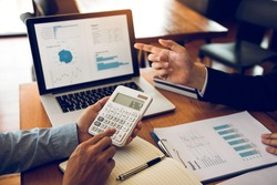 Managers are using tablets to analyze sales cost reports and explain summary reports to employees calculate and record summary information data in the office.