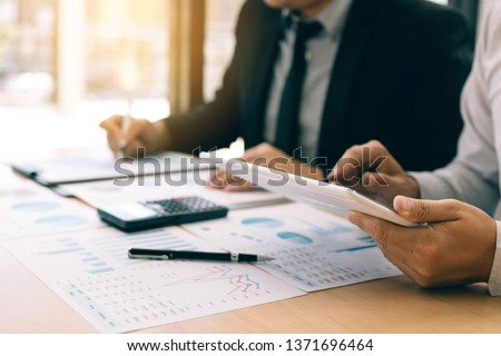 Managers are using tablets to analyze sales cost reports and explain summary reports to employees calculate and record summary information data in the office. #1371696464