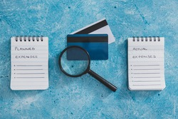 managing money and finance concept, planned expenses vs actual expenses notepads side by side with credit cards and magnifying glass on blue desk