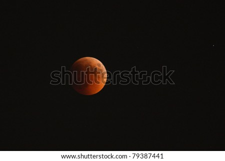 MANAMA, BAHRAIN - APRIL 15-16: Longest lunar eclipse of decade with partial, total and mid eclipse phases observed on June 15-16, 2011 in the sky of Manama, Bahrain. Mid eclipse 15 June at 22:40 - stock photo