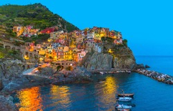 Manarola traditional typical Italian village in National park Cinque Terre with colorful multicolored buildings houses on rock cliff and marine harbor, night evening view, La Spezia, Liguria, Italy