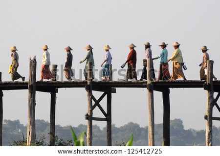 MANDALAY FEB 3 The villagers walking on U-Bein bridge Feb 3 2010 Mandalay Myanmar The bridge is the world longest teak bridge 1.2 km and built across the Taungthaman Lake