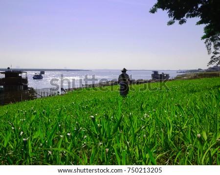 MANDALAY, MYANMAR - DECEMBER 14, 2014: A local Burmese guy in the green field along Irrawaddy river in Mandalay, selective focus #750213205