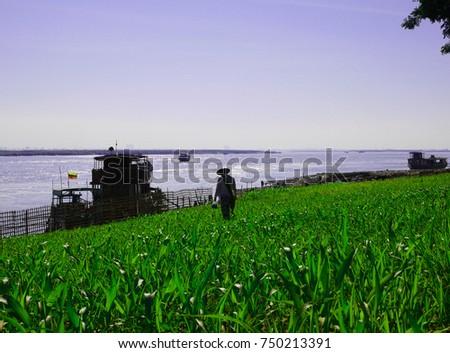 MANDALAY, MYANMAR - DECEMBER 14, 2014: A local Burmese guy in the green field along Irrawaddy river in Mandalay #750213391