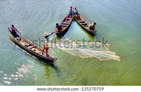 MANDALAY, MYANMAR NOV 20: unidentified  fishermen are fishing on the traditional  way by throwing the net elegant in the water on the Taungthamen Lake on Nov 20, 2011 Mandalay, Myanmar