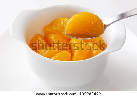 Mandarin oranges from a can, one segment being lifted with a spoon.