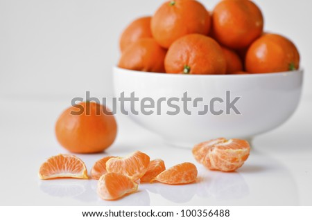Mandarin oranges in a white bowl on white background