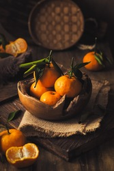 Mandarin oranges on rustic wooden bowl in the dark moody background.