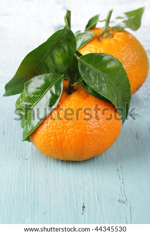 Mandarin oranges with leaves on a wooden table