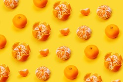 Mandarin pattern on a yellow or orange background, New Year and Christmas concept, peeled tangerines and peeled, mandarin slice. Flat lay