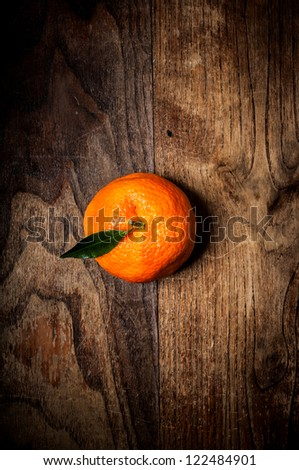 mandarin with leaf on brown wood