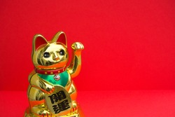Maneki-neko. Japanese and Chinese cat of fortune and luck on a red background with copy space. The cat holds a coin on which there is written