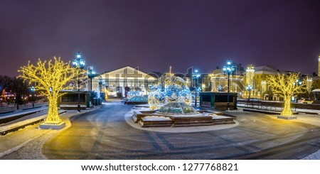 Manezhnaya square and Moscow Manege exhibition hall with the Christmas decoration in winter night. Moscow, Russia.