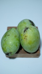 Mangga Harum Manis or Mangga Indramayu or Indramayu mango or sweet fragrant mango is a seasonal fruit. The taste is sweet and a little sour. Selective focus on white area. Green color of Mango