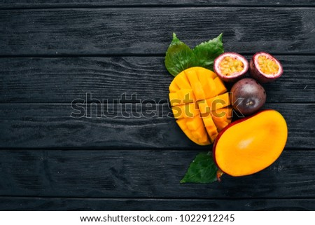 Mango and passion fruit. Fresh Tropical Fruits. On a wooden background. Top view. Copy space.