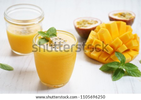 mango and passion fruit smoothies on wooden background