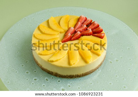 Mango cheesecake decorated with fresh strawberry on glass plate on green background