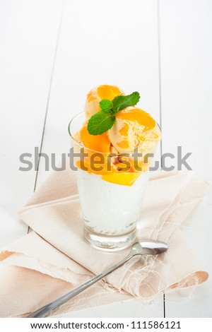 Mango ice cream with fresh mango and whipping cream in a glass