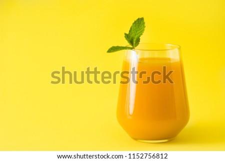 Mango Lassi dessert. Traditional Indian drink on yellow background. Copyspace