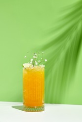 Mango lemonade drink over green background. White table with sunlight and palm leaf hard shadow. Summer, tropical and juicy concept