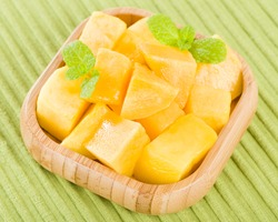 Mango - Pieces of mango in a square bamboo bowl on a green background.