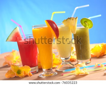 Mango, pineapple, watermelon and kiwi smoothie with drinking straws surrounded by gladiolus flower on wood (Selective Focus, Focus on the mango smoothie in the front)
