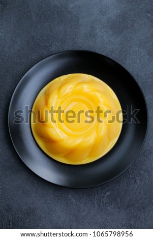 Mango pudding, jelly, dessert on black plate. Slate background. Top view.