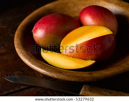 Mango's in wooden bowl with one sliced open