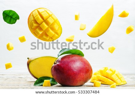 mango with flying slices on a white wood background. tinting. selective focus