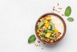 Mango yogurt with granola and kiwi in wooden bowl on white background. Healthy dairy product breakfast